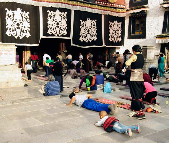 Tibetan Pilgrims Prostrating in front of the Jokhang Temple