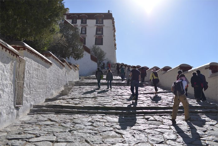 Tourists are ascending the white palace of Potala Palace