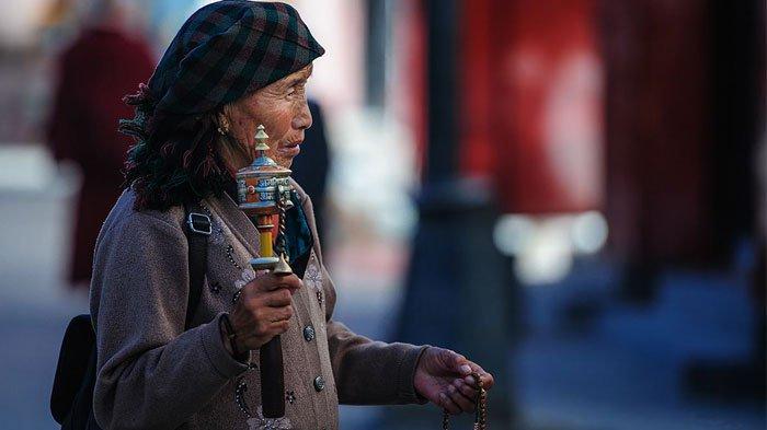 Tibetan pilgrim with a prayer wheel