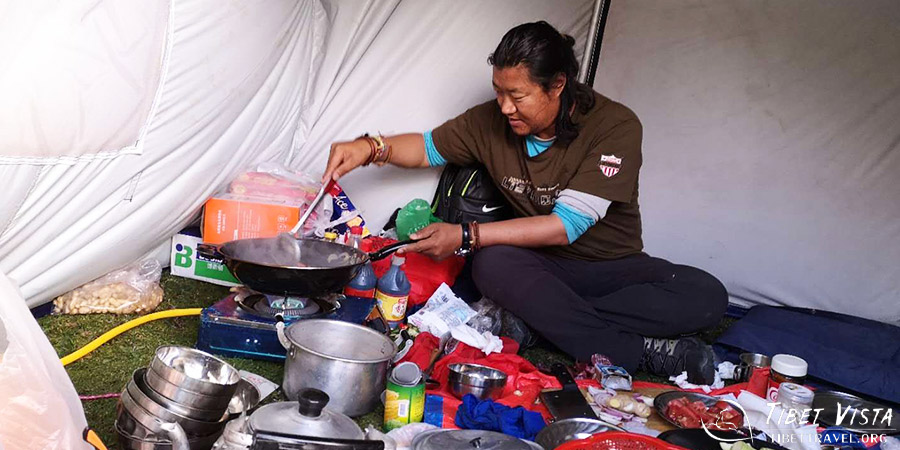 Our Tibetan guide is cooking dishes for clients during the trekking